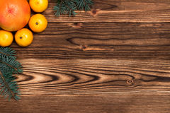 Christmas and New Year Mandarins next to the Christmas tree branches with cones on a wooden background Royalty Free Stock Photography