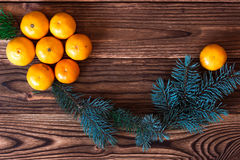 Christmas and New Year Mandarins next to the Christmas tree branches with cones on a wooden background Stock Photo