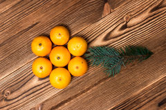 Christmas and New Year Mandarins next to the Christmas tree branches with cones on a wooden background Stock Images