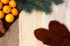 Christmas and New Year Mandarins next to the colorful knitted sweaters, cones, branches of the Christmas tree and knit gloves on a. A Christmas and New Year Royalty Free Stock Photo