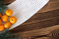 Christmas and New Year Mandarins next to the colorful knitted sweaters, cones, branches of the Christmas tree on a wooden backgrou Stock Photos