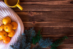 Christmas and New Year Mandarins next to the colorful knitted sweaters, cones, branches of the Christmas tree on a wooden backgrou Stock Photo