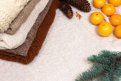 Christmas and New Year Mandarins in the snow next to the multi-colored sweaters, pine cones and Christmas tree branch. A Christmas and New Year Mandarins in the Royalty Free Stock Photo