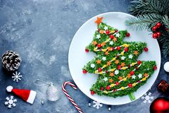 Christmas new year meal idea - creative appetizer salad like a christmas tree. With festive decoration from greens and vegetables stock photos