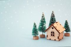 Christmas and New Year miniature house with fir trees on blue b. Ackground. Copy space for text. Winter card. Holiday and celebration concept stock image