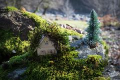 Christmas and New Year miniature house at forest in the sunlight. Little toy house close up. Festive background. Christmas. Decorations. Holiday and celebration stock photography