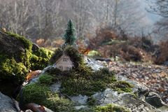 Christmas and New Year miniature house at forest in the sunlight. Little toy house close up. Festive background. Christmas. Decorations. Holiday and celebration stock photos