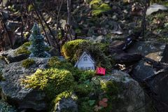 Christmas and New Year miniature house at forest in the sunlight. Little toy house close up. Festive background. Christmas. Decorations. Holiday and celebration royalty free stock photos