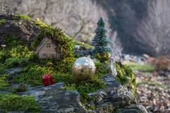 Christmas and New Year miniature house at forest in the sunlight. Little toy house close up. Festive background. Christmas. Decorations. Holiday and celebration stock images