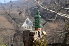 Christmas and New Year miniature house at forest in the sunlight. Little toy house close up. Festive background. Christmas. Decorations. Holiday and celebration stock image