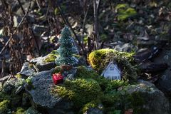 Christmas and New Year miniature house at forest in the sunlight. Little toy house close up. Festive background. Christmas. Decorations. Holiday and celebration royalty free stock images