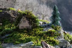 Christmas and New Year miniature house at forest in the sunlight. Little toy house close up. Festive background. Christmas. Decorations. Holiday and celebration royalty free stock photo