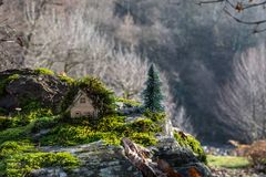 Christmas and New Year miniature house at forest in the sunlight. Little toy house close up. Festive background. Christmas. Decorations. Holiday and celebration royalty free stock photography