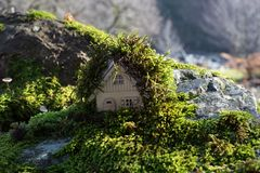Christmas and New Year miniature house at forest in the sunlight. Little toy house close up. Festive background. Christmas. Decorations. Holiday and celebration royalty free stock image