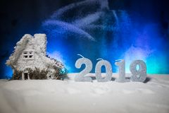 Christmas and New Year miniature house in the snow at night with fir tree. Little toy house on snow with tree. Festive background. Christmas decorations royalty free stock images
