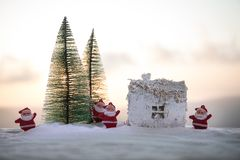 Christmas and New Year miniature house in the snow in the sunlight. Little toy house on snow with tree. Festive background. Christmas decorations. Holiday and stock photos