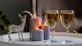 New Year`s decor: two glasses with champagne, burning candles, a Christmas tree and a decorative statue of a deer on a white table royalty free stock photo