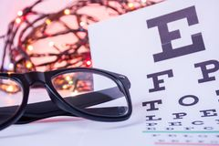 Christmas and New Year in ophthalmology optometry. Eyeglasses and ophthalmological table for visual acuity test in foreground with. Blurred lights bulbs royalty free stock photo