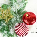 Christmas or New Year ornament on a white wooden surface. Christmas or New Year ornament. Sprigs of fir and bright decorations on a white wooden surface stock image