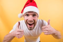 Christmas and new year party. Man santa with thumbs up hands on orange background. Santa claus fashion. Macho smile in red xmas hat and white tshirt. Winter Royalty Free Stock Photos