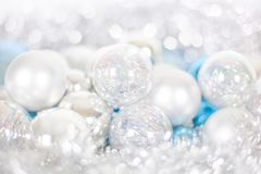 Christmas and New Year pattern, ornament of Christmas balls and tinsel, winter fairytale decor in blue and white color. Lights bokeh closeup, copy space royalty free stock photos