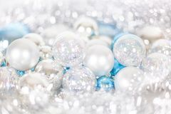 Christmas and New Year pattern, ornament of Christmas balls and tinsel, winter fairytale decor in blue and white color. Lights bokeh closeup, copy space royalty free stock photo