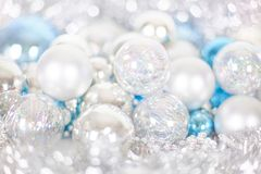 Christmas and New Year pattern, ornament of Christmas balls and tinsel, winter fairytale decor in blue and white color. Lights bokeh closeup, copy space royalty free stock image