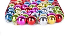 Christmas and New Year pattern, ornament of bright multi-colored glass decorative balls, shining lights and sparkles, bokeh. On white background isolated close royalty free stock photography