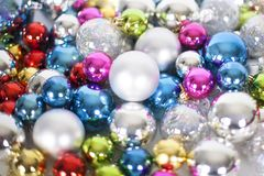 Christmas and New Year pattern, ornament of bright multi-colored glass decorative balls and tinsel, lights and sparkles, closeup. Copy space royalty free stock photography