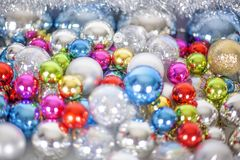Christmas and New Year pattern, ornament of bright multi-colored glass decorative balls and tinsel, lights and sparkles, closeup. Copy space stock images
