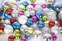 Christmas and New Year pattern, ornament of bright multi-colored glass decorative balls and tinsel, lights and sparkles, closeup. Copy space stock image