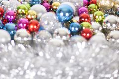 Christmas and New Year pattern, ornament of bright multi-colored glass decorative balls and tinsel, lights and sparkles, closeup. Copy space stock photo