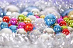 Christmas and New Year pattern, ornament of bright multi-colored glass decorative balls and tinsel, lights and sparkles, closeup. Copy space royalty free stock photos