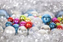 Christmas and New Year pattern, ornament of bright multi-colored glass decorative balls and tinsel, lights and sparkles, closeup. Copy space royalty free stock image