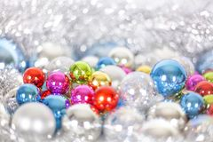 Christmas and New Year pattern, ornament of bright multi-colored glass decorative balls and tinsel, lights and sparkles, closeup. Copy space stock photography
