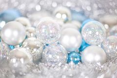 Christmas and New Year pattern, ornament of Christmas balls and tinsel, winter fairytale decor in blue and white color. Lights bokeh closeup, copy space stock photo