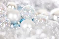 Christmas and New Year pattern, ornament of Christmas balls and tinsel, winter fairytale decor in blue and white color. Lights bokeh closeup, copy space royalty free stock images