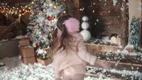 Christmas or New Year. portrait of a child in Christmas decorations. little girl in a fur headphones throws up the snow. Christmas or New Year. Children in light stock video footage
