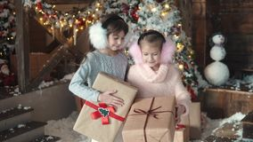 Christmas or New Year. portrait of two little girls holding beautifully packaged gifts. children received gifts for. Christmas or New Year. a little girl hanging stock footage