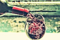 Pouring wine. Red wine in a glass. Sommelier wine into the glass on a blue background old. Royalty Free Stock Image