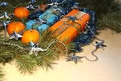 Christmas and New Year presents in orange and blue boxes lie under a Christmas tree next to tangerines and tinsel. Royalty Free Stock Photos