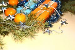 Christmas and New Year presents in orange and blue boxes lie under a Christmas tree next to tangerines and tinsel. Royalty Free Stock Photo