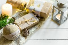 Christmas New Year presents packaging. Gift boxes in craft paper tied with twine hand made fabric ornament ball white sweater royalty free stock image