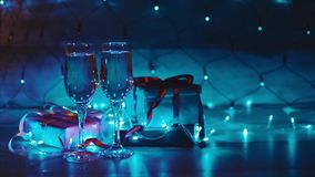 Christmas and new year presents two glasses of champagne blue garland background stock video