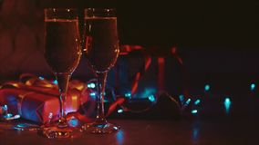 Christmas and new year presents two glasses of champagne blue garland background. Close up shot of christmas and new year gift boxes and two glasses of bubbling stock footage