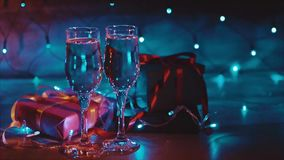 Christmas and new year presents two glasses of champagne blue garland background. Close up shot of christmas and new year gift boxes and two glasses of bubbling stock video