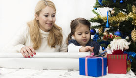 Christmas and New Year presents. Young mother and daughter preparing presents for family for holidays Christmas eve and New Year Royalty Free Stock Photos