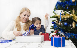 Christmas and New Year presents. Young mother and daughter preparing presents for family for holidays Christmas eve and New Year Stock Images
