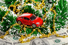 Christmas and new year red car toy through the dollars. (installation on the theme of New Year and Christmas business Stock Photos