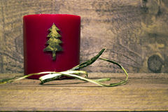 Christmas New Year red wax candle with a Christmas tree pattern. On a dark wooden background Stock Photos